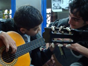 Jeune de l'association apprenant la guitare